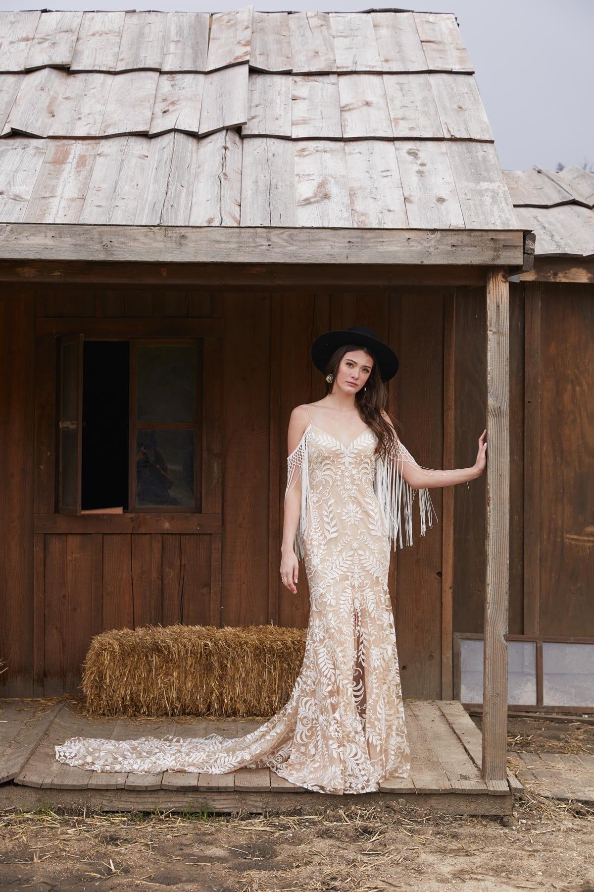 Model mit Bohokleid vor einer Hütte